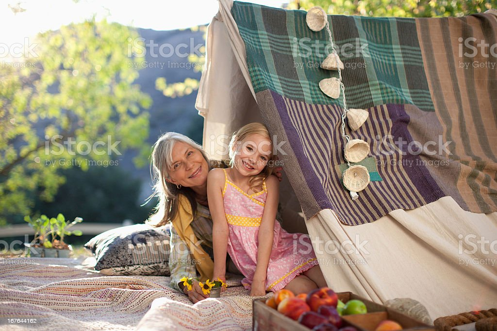 Older woman and granddaughter sitting in tent royalty-free stock photo