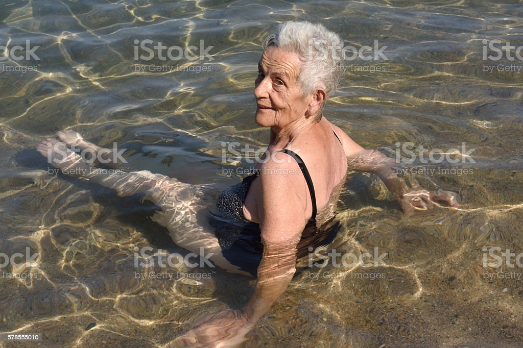 older woman bathing in the sea, stock photo