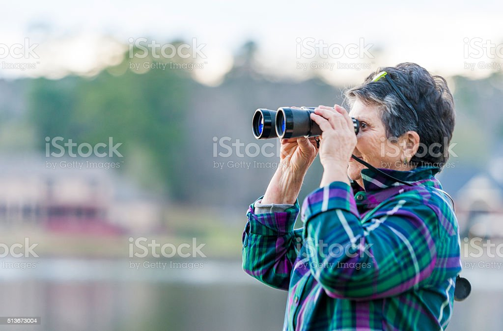 Older Woman Birdwatching by the Lake stock photo