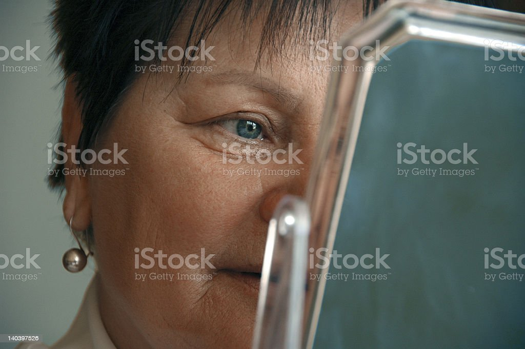Older Woman Examining Her Face In The Mirror royalty-free stock photo