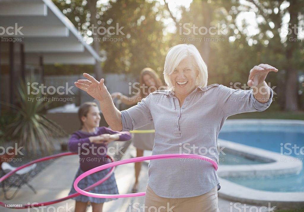 Older woman hula hooping in backyard stock photo