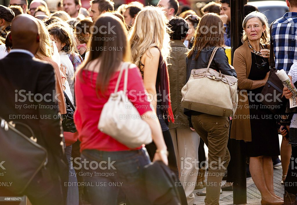 Older woman in a crowded intersection royalty-free stock photo