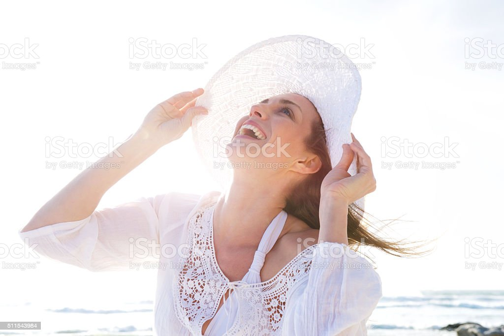 Older woman laughing with hat at the beach stock photo