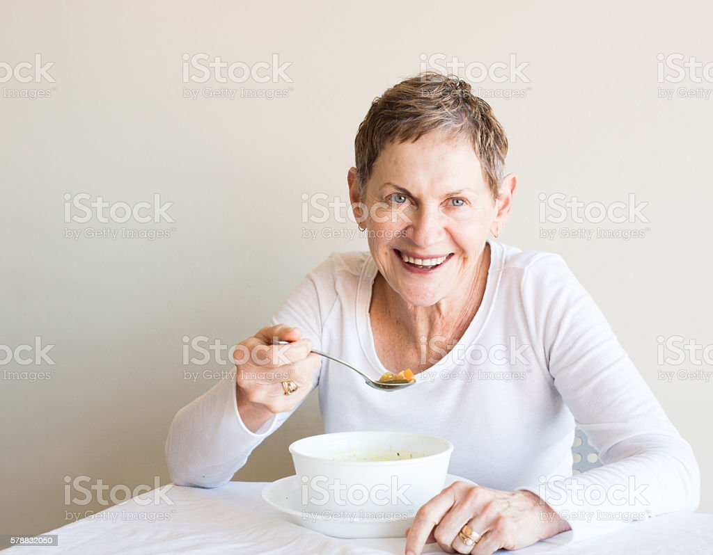Older woman laughing with soup stock photo