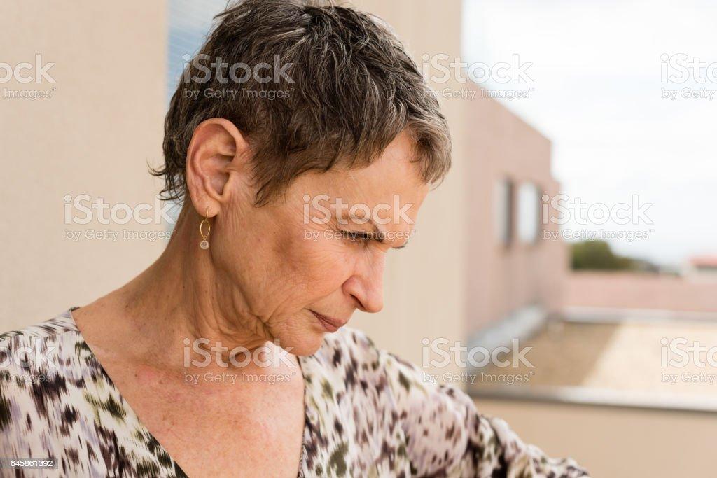 Older woman looking pensive stock photo