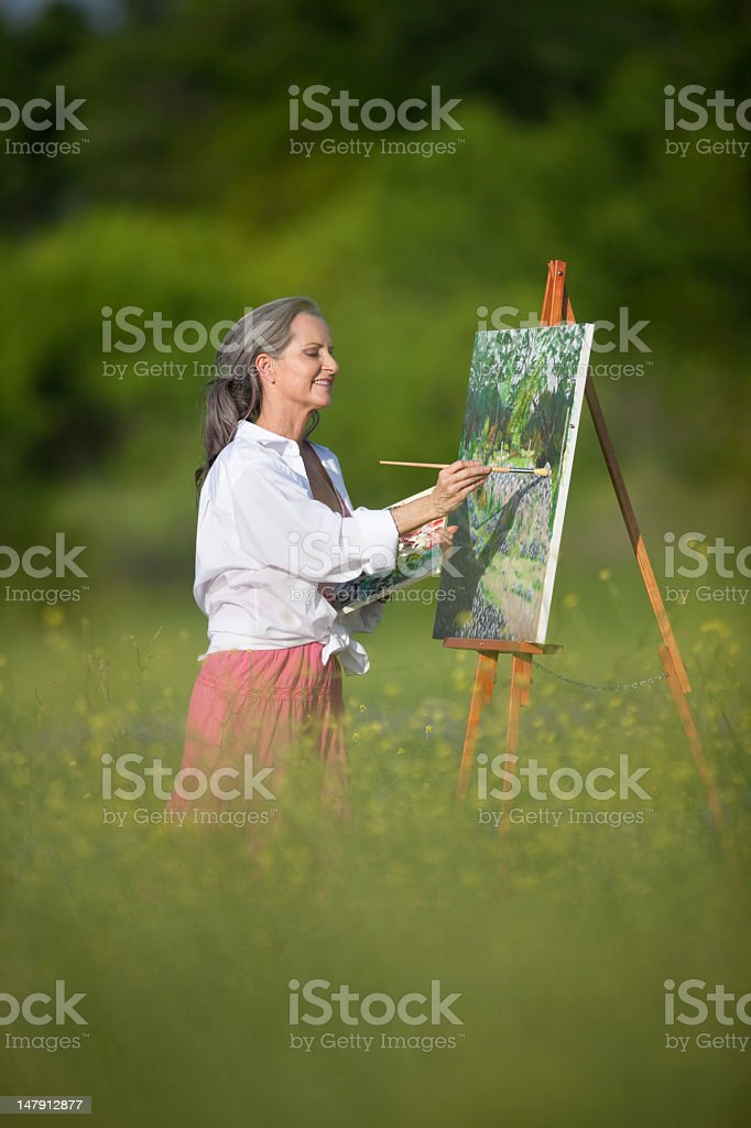 Older Woman Oil Painting in Field of Wildflowers royalty-free stock photo