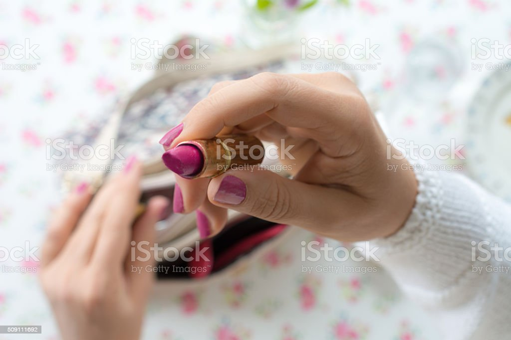 Older woman opens her lipstick stock photo