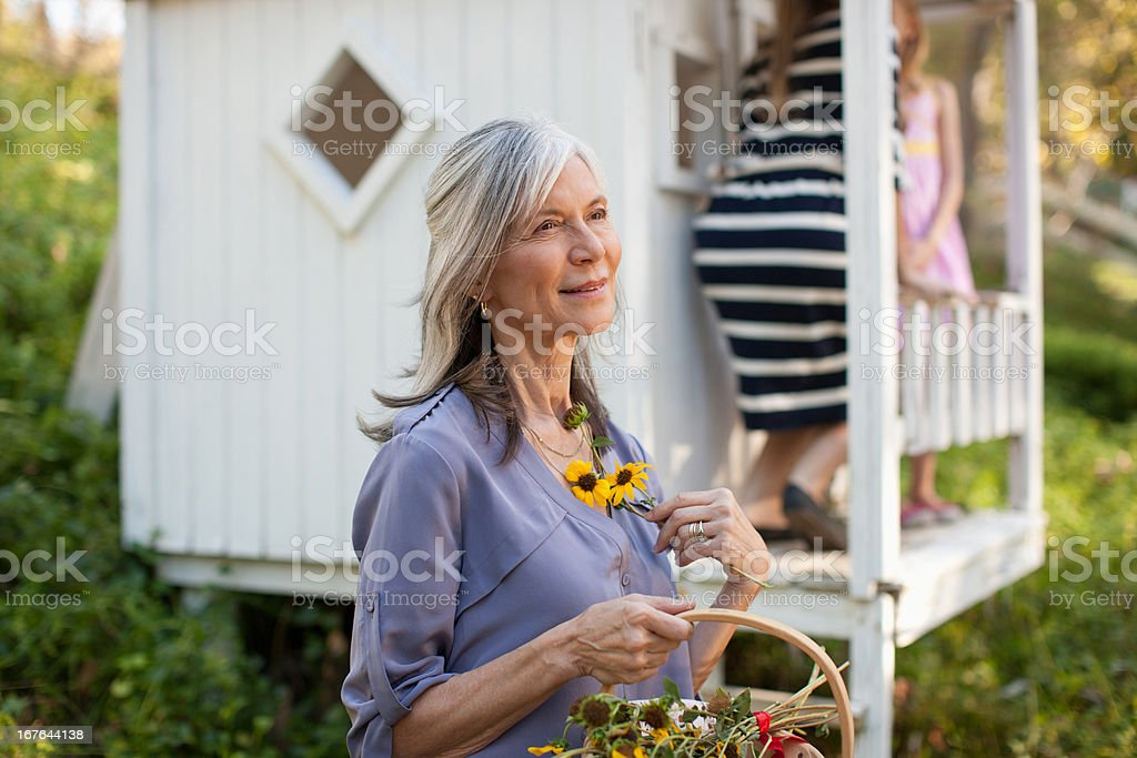 Older woman picking flowers outdoors royalty-free stock photo
