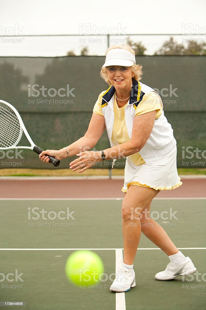 Older woman playing tennis in yellow and white outfit royalty-free stock photo