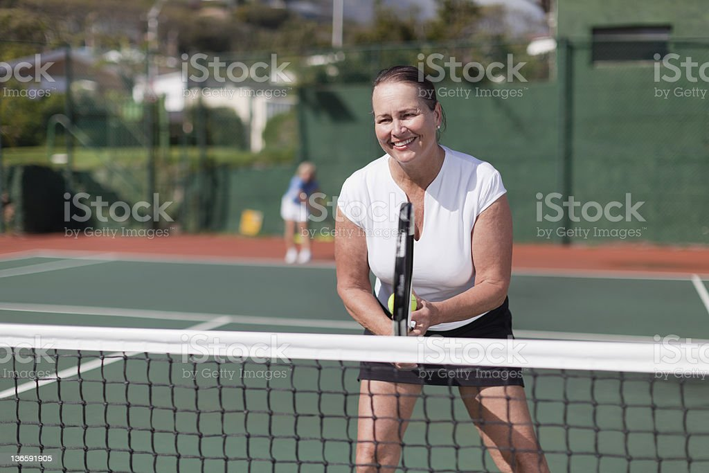 Older woman playing tennis on court royalty-free stock photo