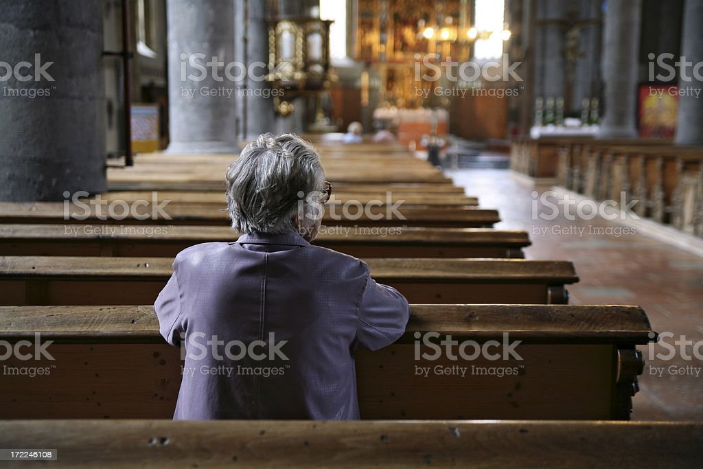 Older woman praying in an almost empty church, rear view stock photo