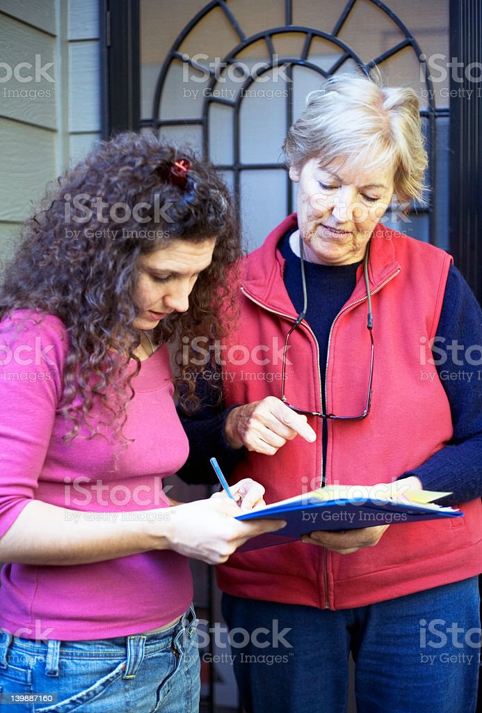 Older woman talking to younger woman holding a clipboard royalty-free stock photo