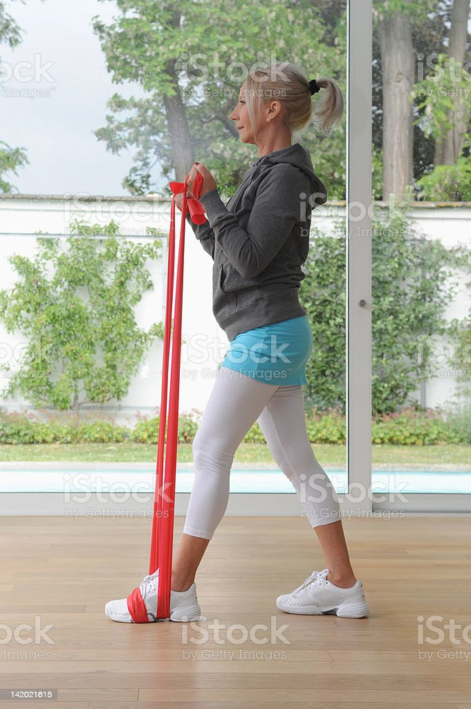 Older woman using exercise band at home stock photo