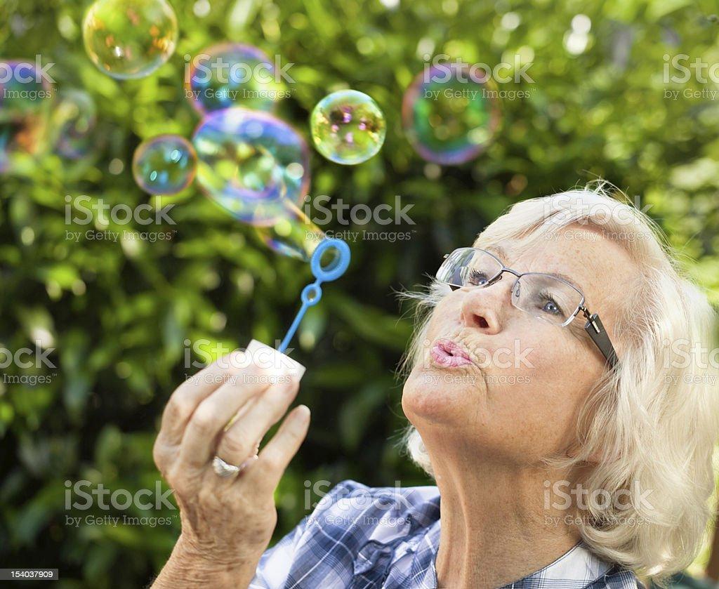 Older woman wearing blue plaid shirt blowing bubbles stock photo