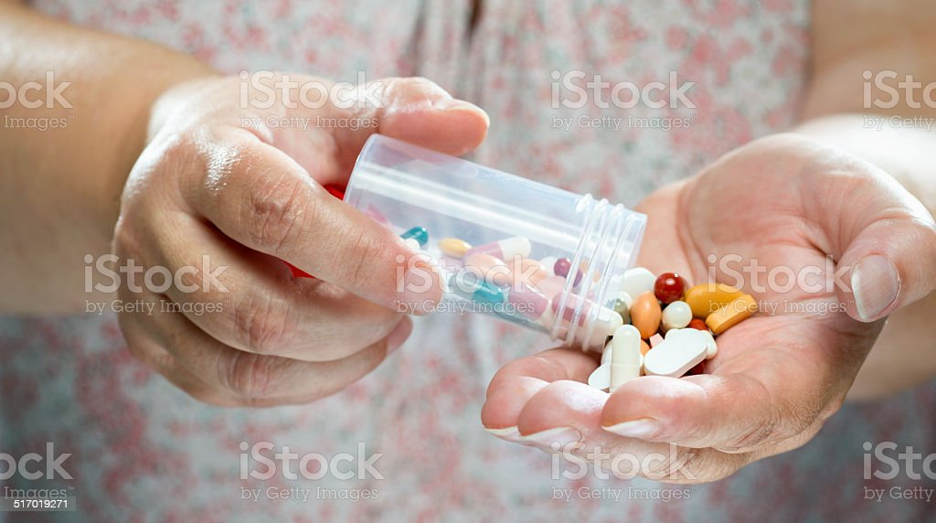 Older women pouring medicine into hand. stock photo