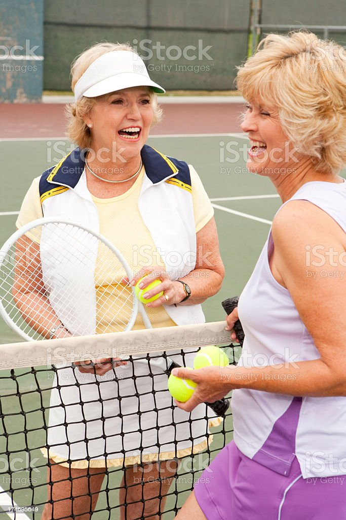 Older women with rackets on a tennis court royalty-free stock photo