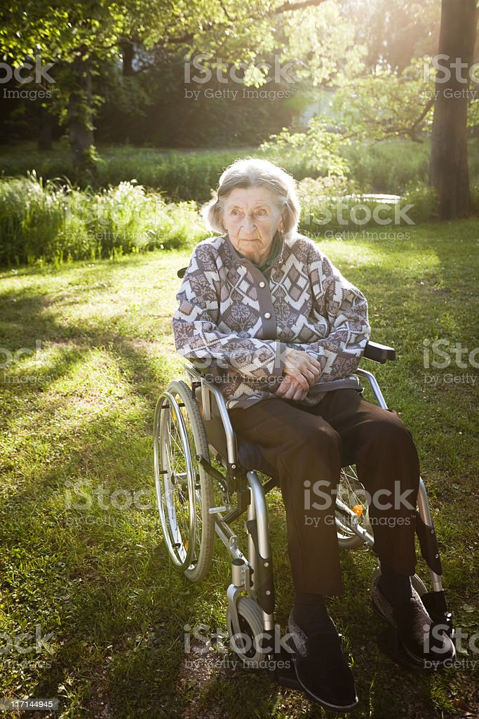 Oldery Woman Resting in Shade of Trees stock photo