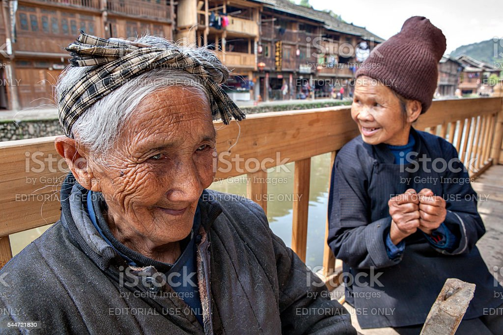 Oldest Chinese Peasant woman resting on bench in rural street. stock photo