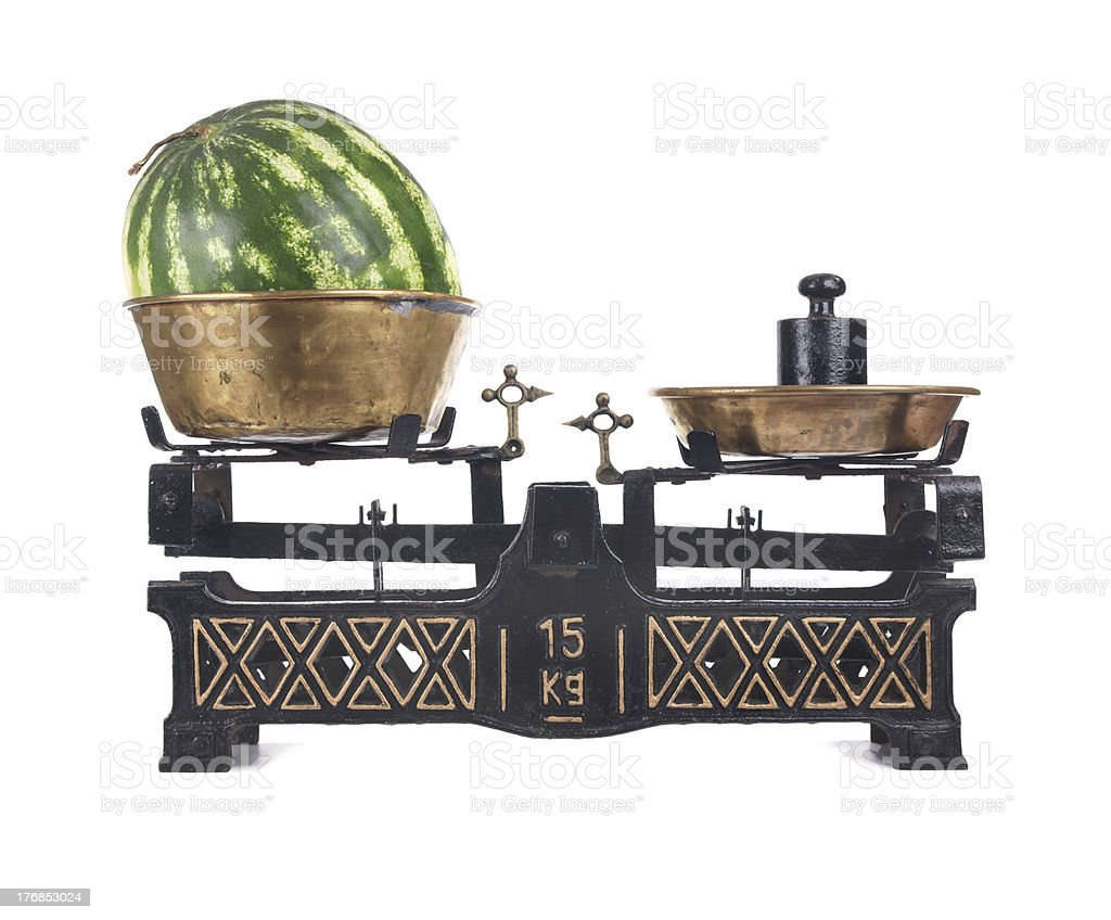 Old-fashioned balance scale with watermelon isolated on white background royalty-free stock photo