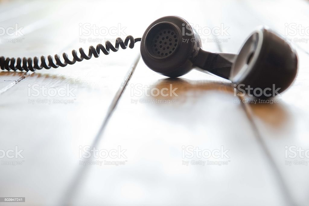 Old-fashioned brown telephone receiver lying on floor stock photo