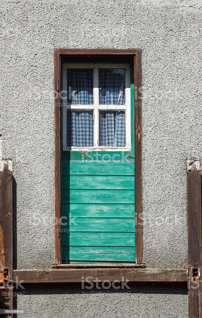 Old-fashioned green wooden door with small window stock photo