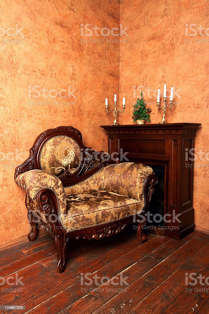 old-fashioned interior with luxury armchair, fireplace, candelabras  and Christmas tree royalty-free stock photo