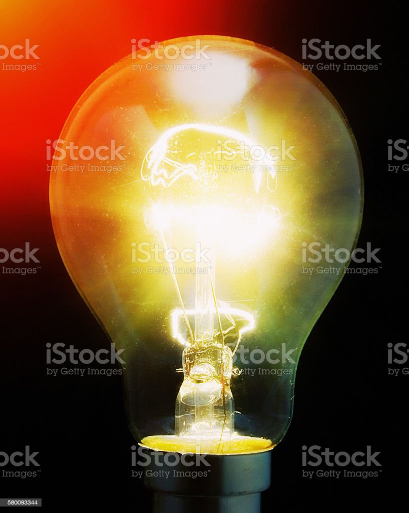Old-fashioned light bulb burning  brightly with filament glowing, dark background stock photo