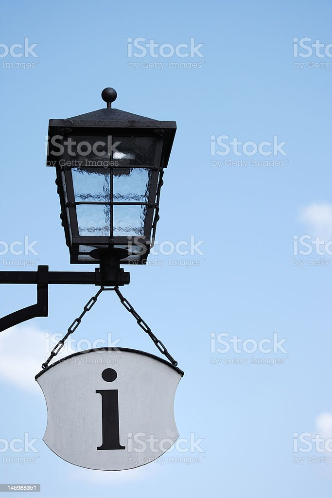 old-fashioned street light and information symbol against blue sky, Germany royalty-free stock photo