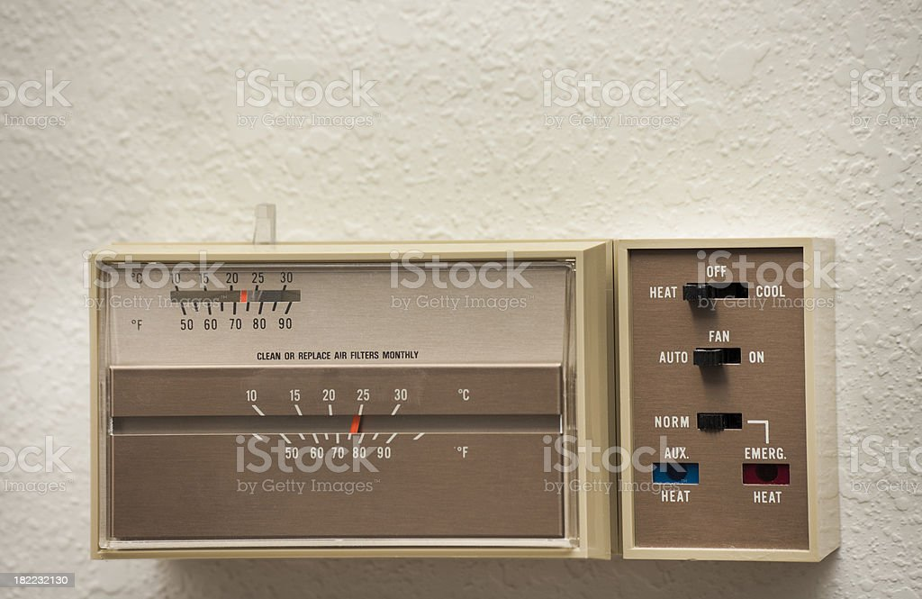 old-fashioned thermostat for heat pump on wall in home stock photo