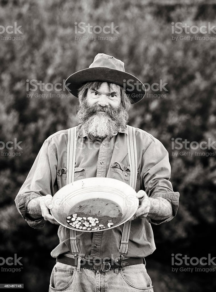 Old-fashioned Western prospector showing his pan black and white stock photo
