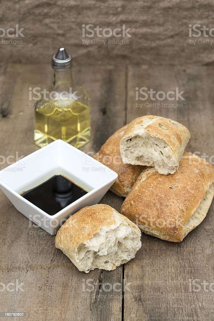 Olive bread rolls in rustic kitchen setting with utensils royalty-free stock photo