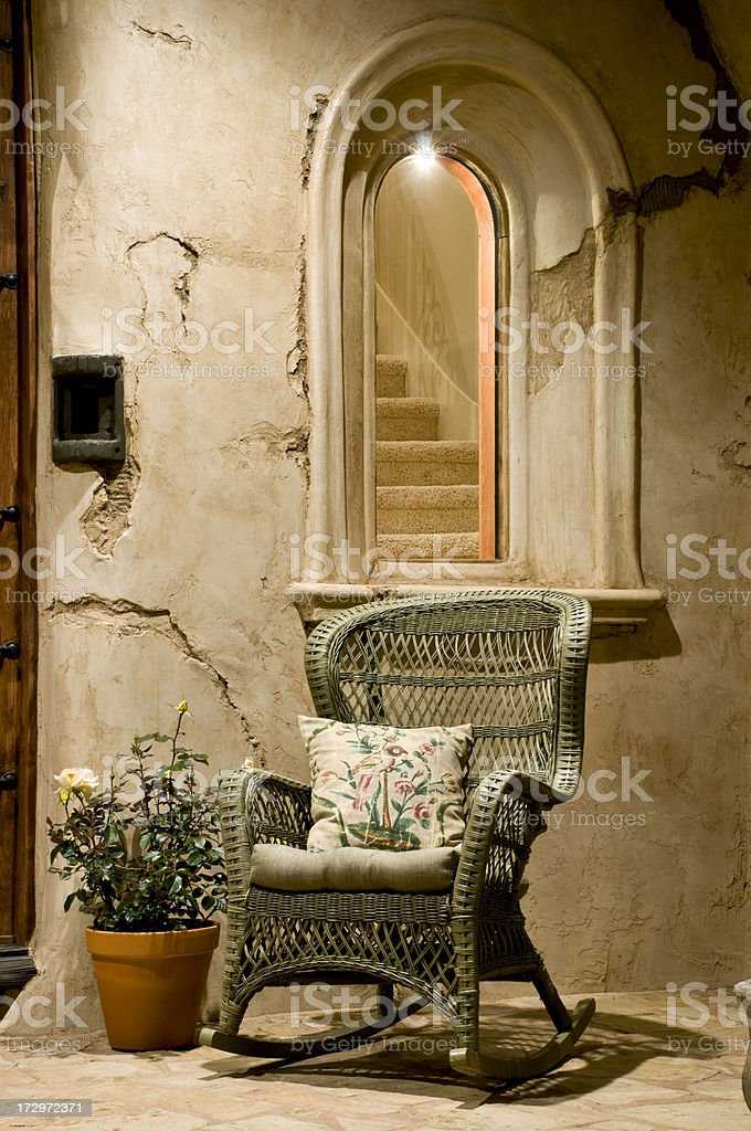 Olive green wicker rocking chair on front porch royalty-free stock photo