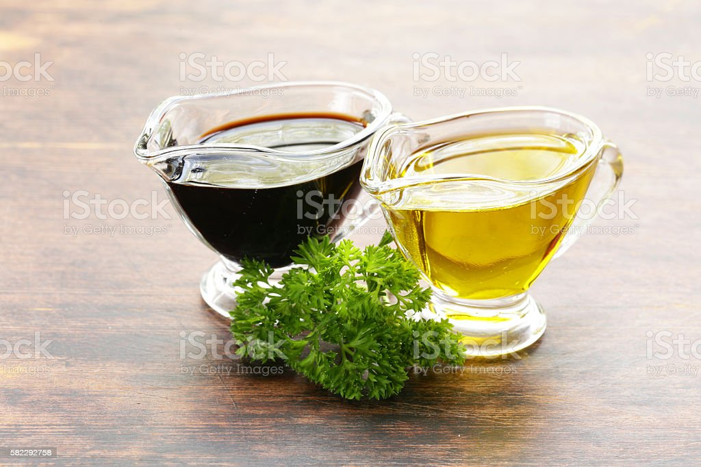 olive oil and balsamic vinegar in a glass gravy boat stock photo