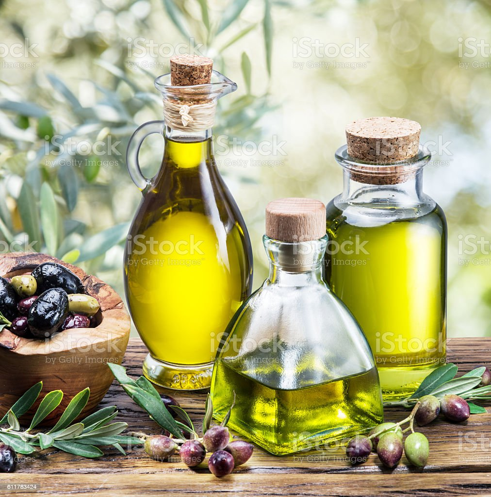 Olive oil and berries are on the wooden table. stock photo