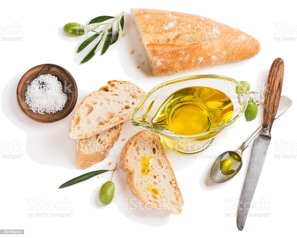 Olive oil and slices of baguette, above view. stock photo