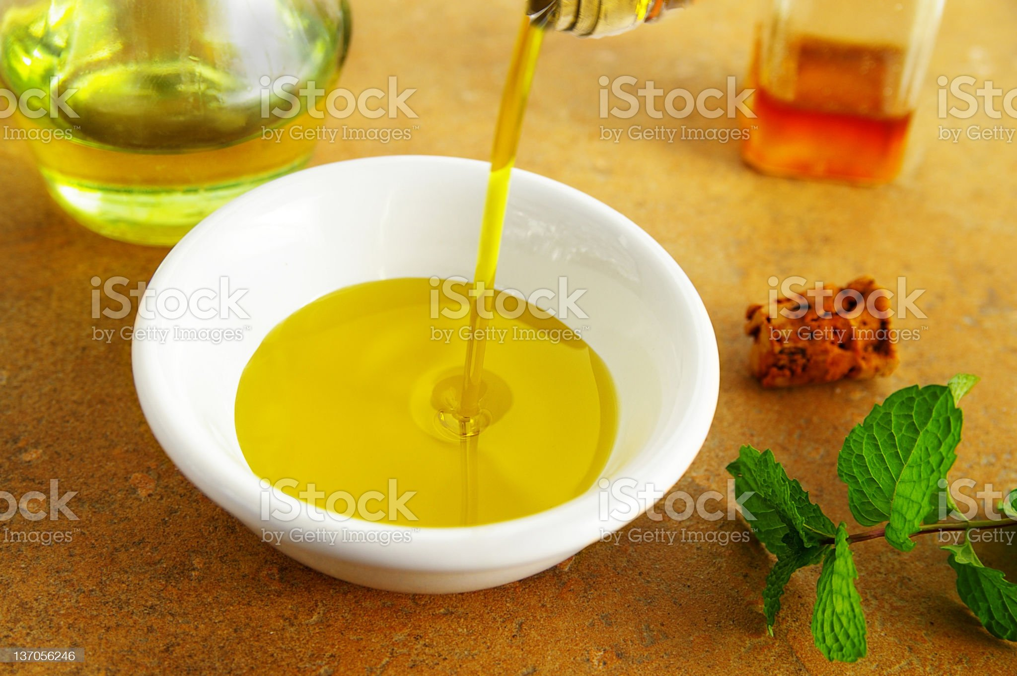 Olive oil being poured into a white bowl royalty-free stock photo