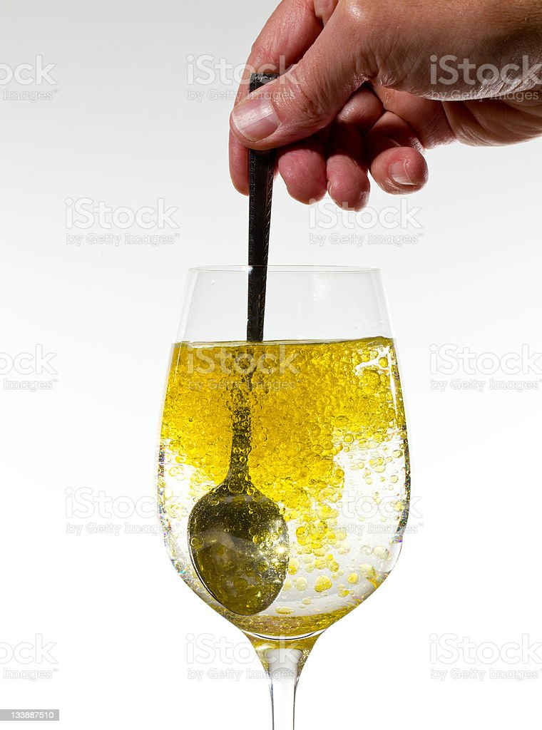 Olive oil being stirred in wine glass stock photo