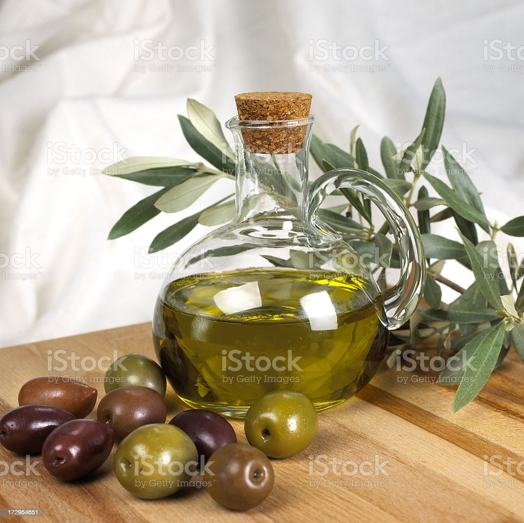 Olive oil bottle and olives on a wooden surface stock photo