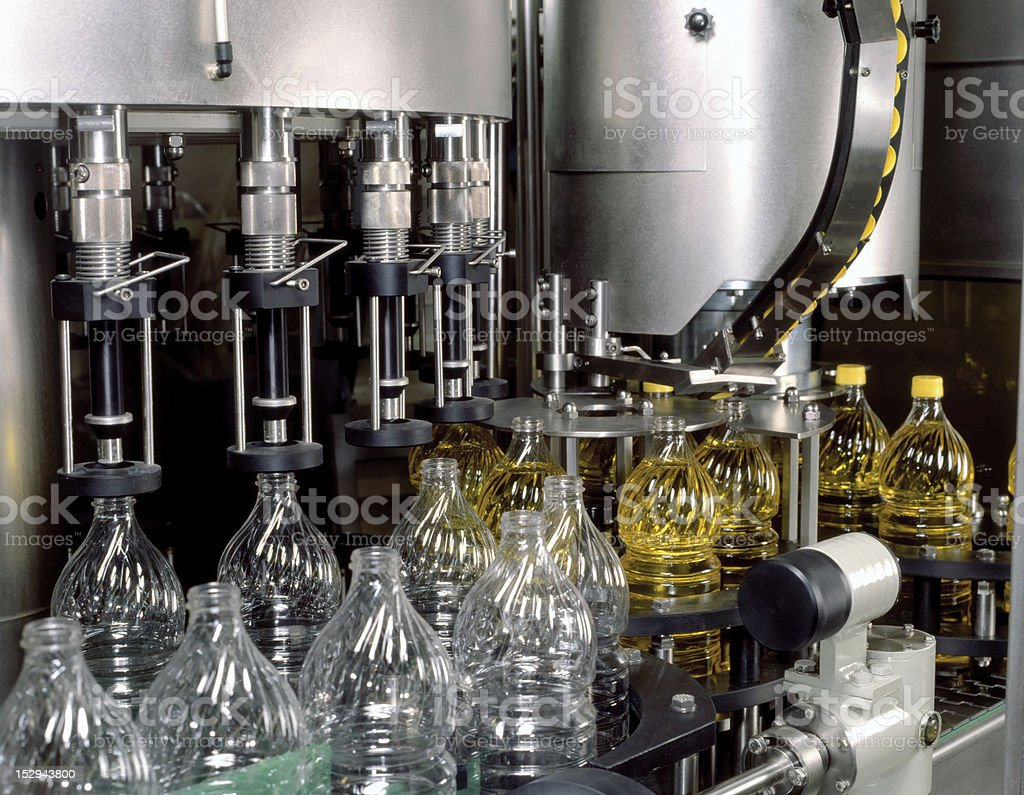 Olive oil bottles being filled at a factory royalty-free stock photo