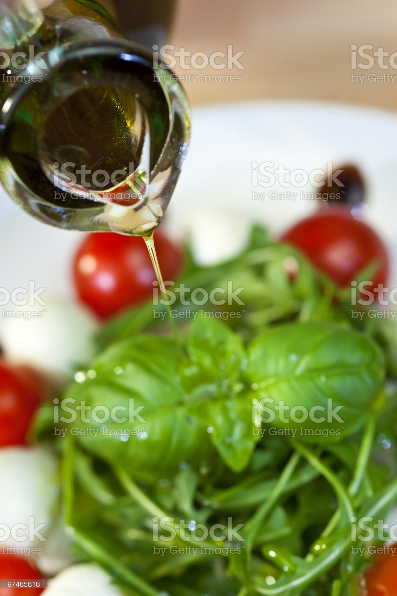 Olive Oil Dressing Pouring Onto Fresh Salad royalty-free stock photo