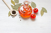 olive oil in jar on wooden background with spices