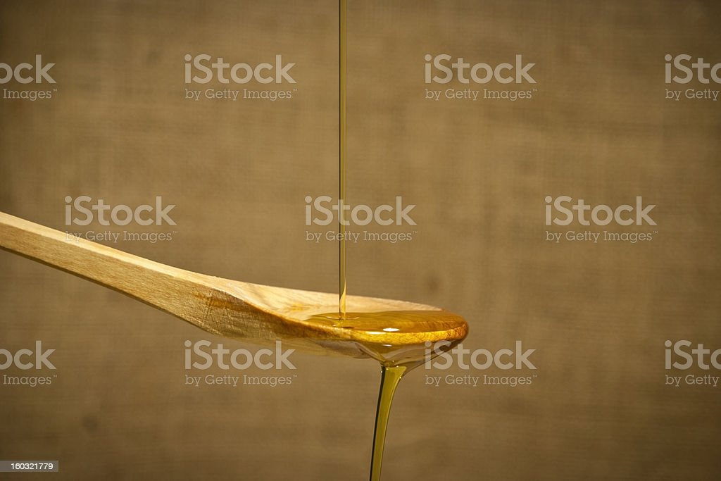 Olive oil over the wooden spoon royalty-free stock photo