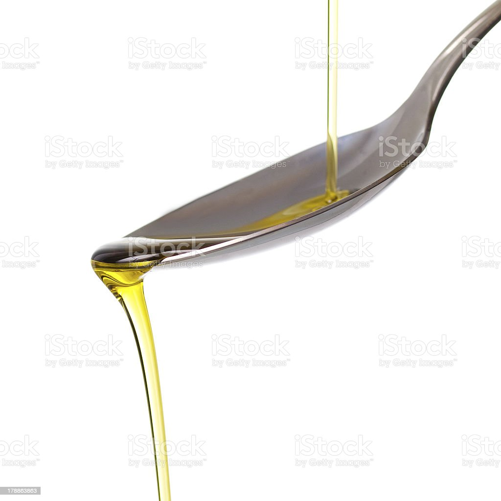 Olive oil pouring on a spoon stock photo