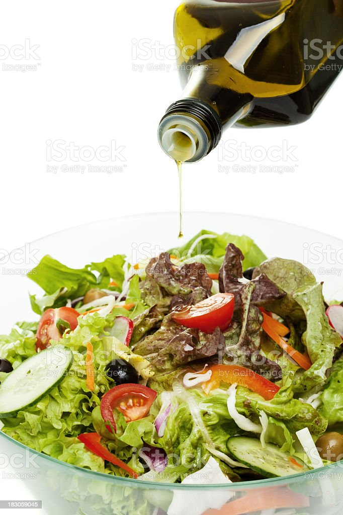 Olive oil pouring over salad stock photo