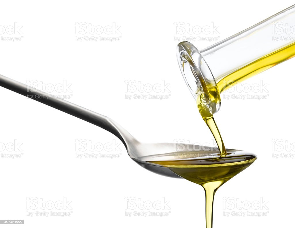 Olive Oil pouring over tablespoon stock photo