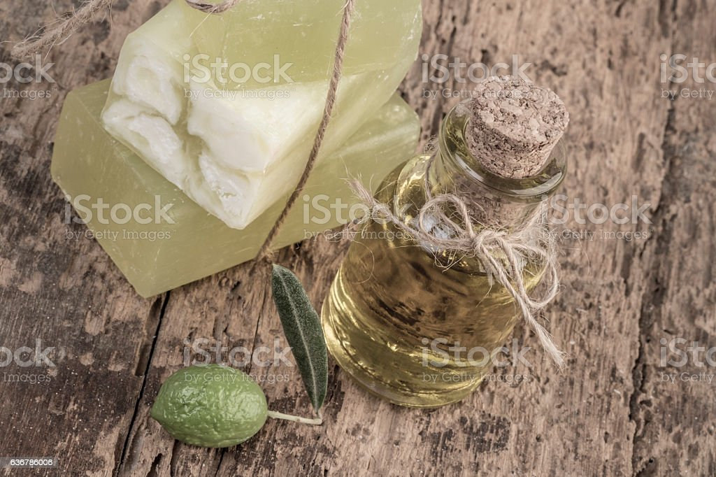 Olive oil soap bar and oil bottle on wooden table stock photo