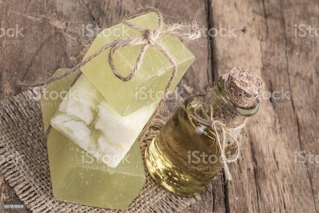 olive oil soap bars and oil bottle on wooden table stock photo
