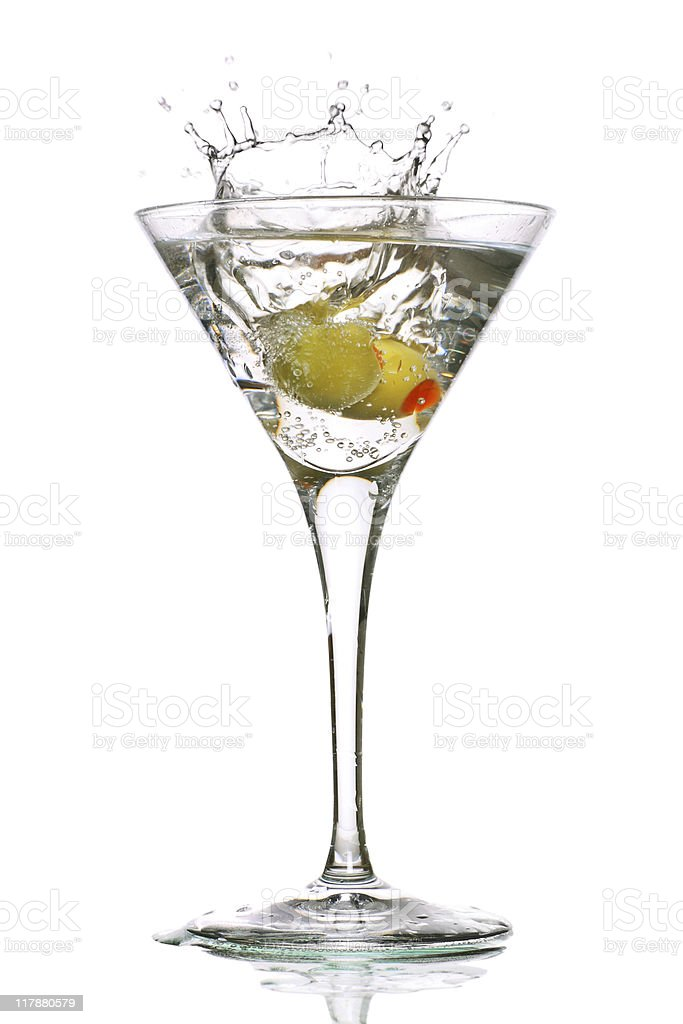 Olive splashing into a clear martini in glass stock photo