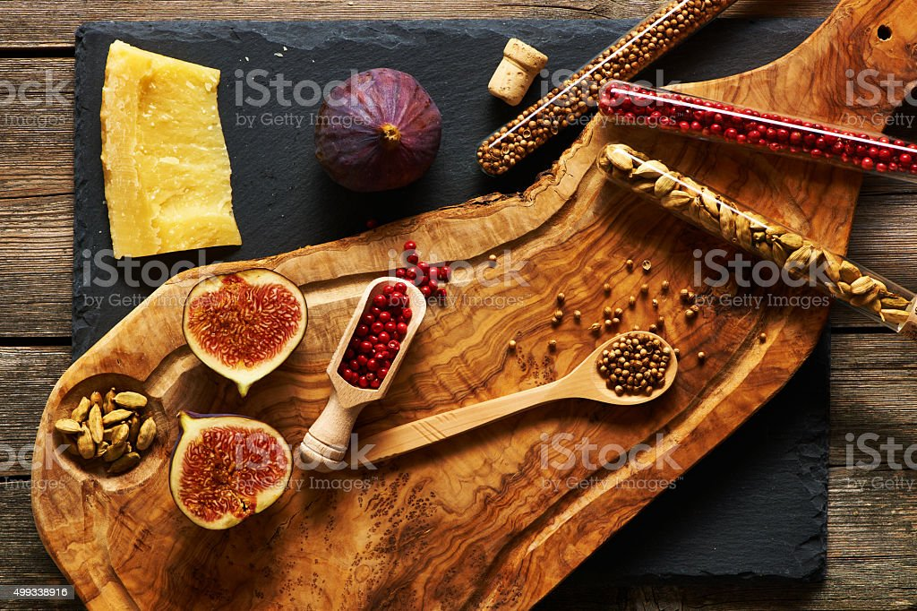 Olive wood cutting board with spices and fig stock photo
