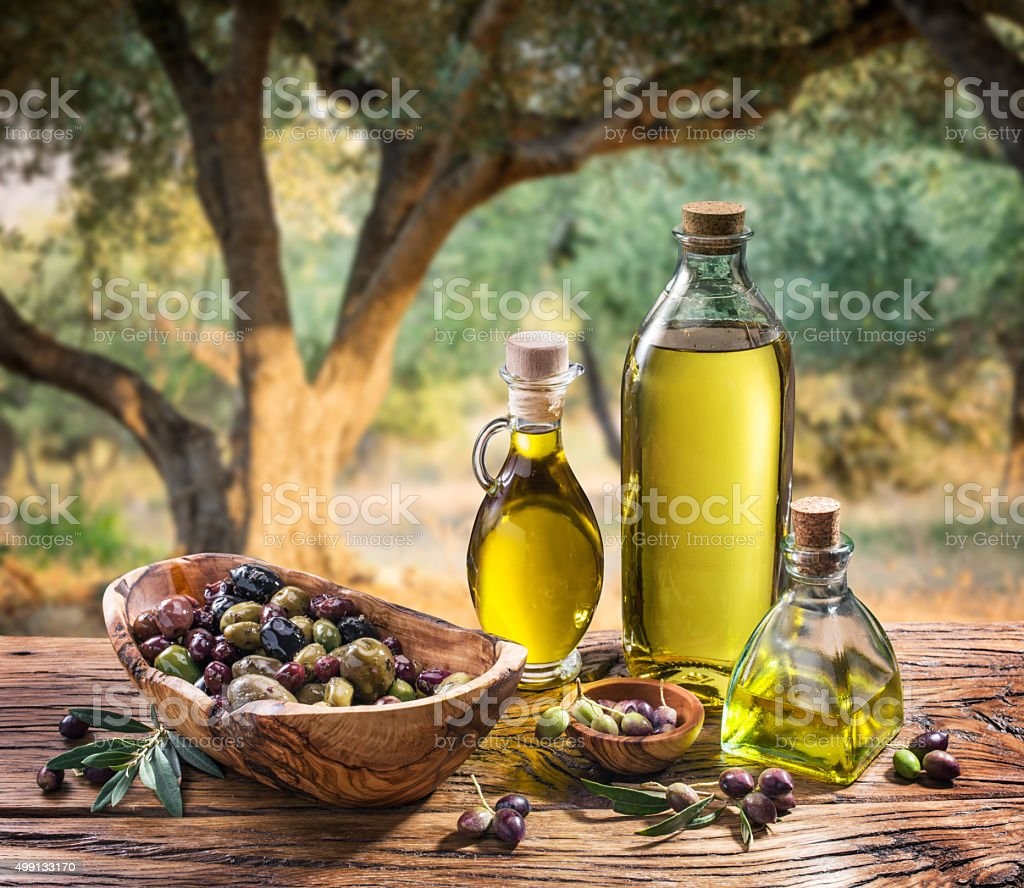 Olives and olive oil on the nature background. stock photo